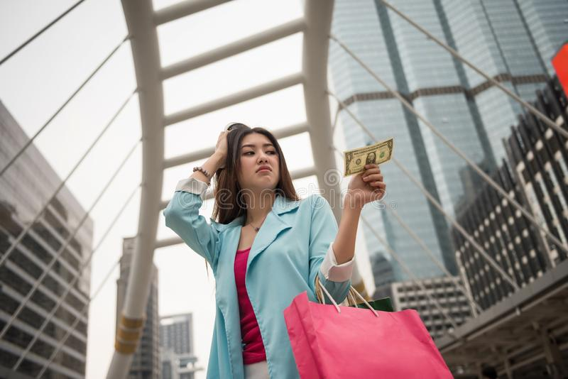 Sad broke shopaholic Asian girl. Sad shopaholic Asian girl look at one Dollar bill in hand with headache sign. No more money to shopping in super discount on stock photography