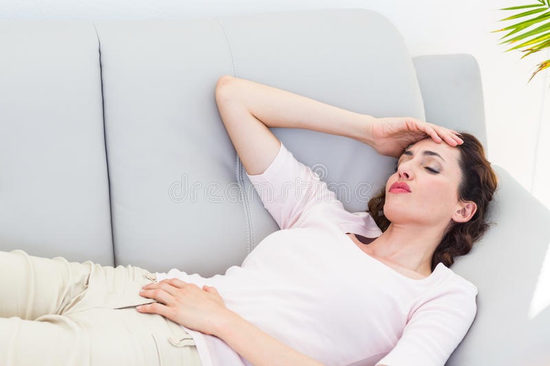 Sad brunette lying on the couch. On white background royalty free stock images