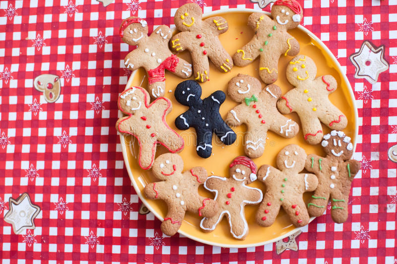 Sad burnt gingerbread man among finished with royalty free stock photography