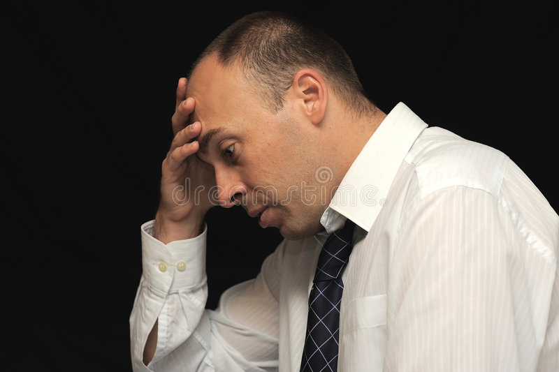 Sad Business Man. Profile head and shoulders shot of a sad businessman with his hand resting on his forehead. Isolated on a black background