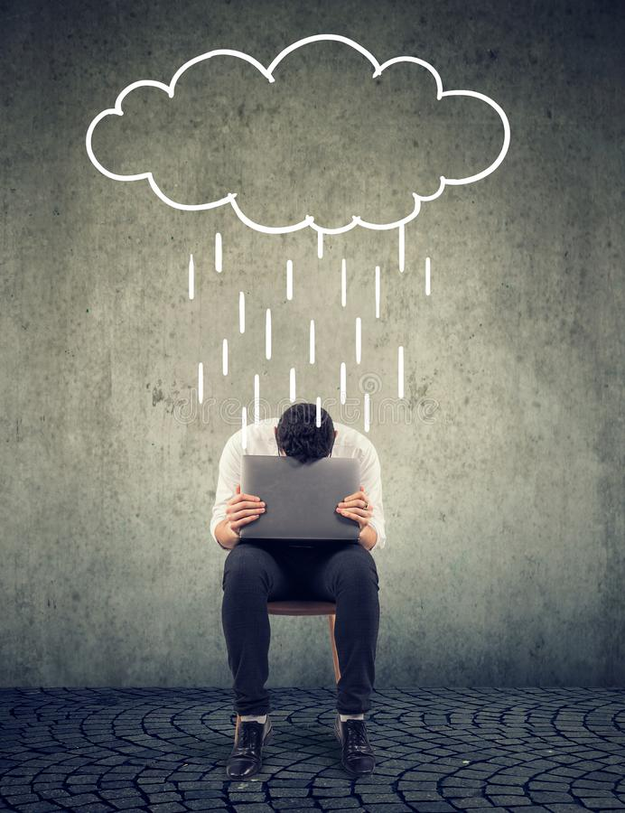 Sad business man sitting on a chair with laptop looking down with a rain cloud above stock illustration