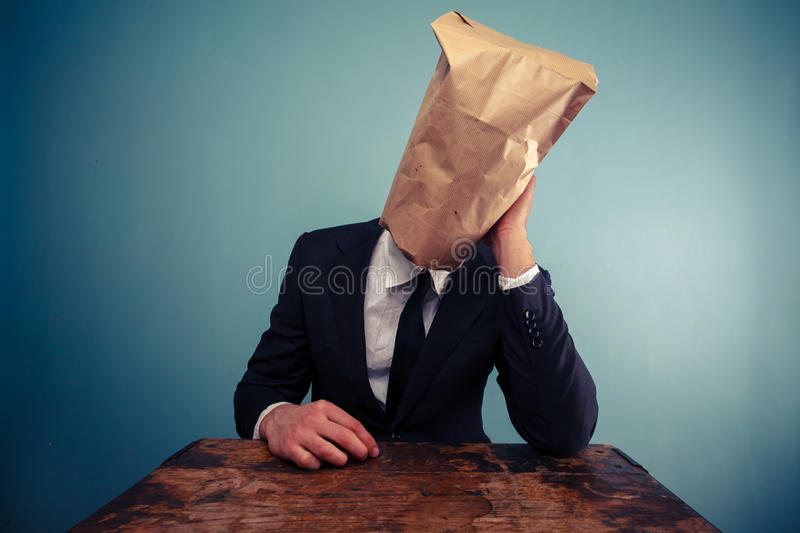 Sad businessman with bag over his head stock images
