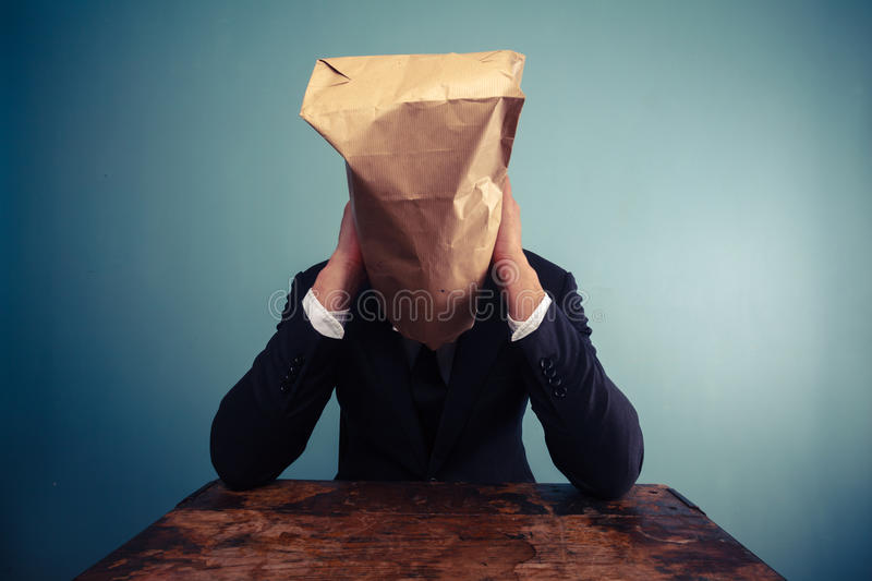 Sad businessman with bag over his head royalty free stock image