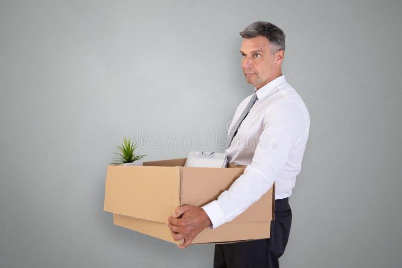 Sad Businessman Carrying Belongings In Cardboard Box. Side View Of A Sad Businessman Carrying Belongings In Cardboard Box On Grey Background royalty free stock image
