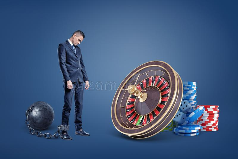 A sad businessman chained to an iron ball stands near a casino roulette and chip stacks. stock image