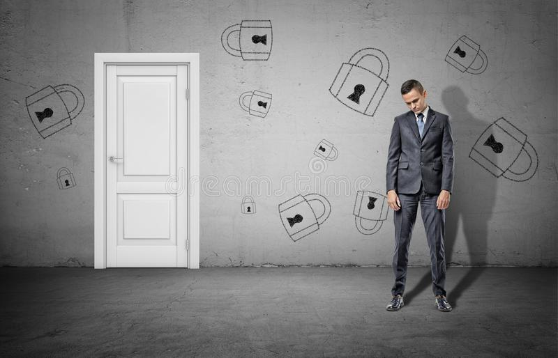 A sad businessman with his head low stands near a closed white door and a concrete wall with many drawn padlocks. stock images