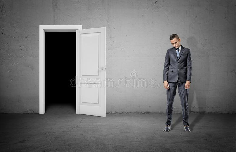A sad businessman with his head low stands near a door frame showing complete darkness. stock photography