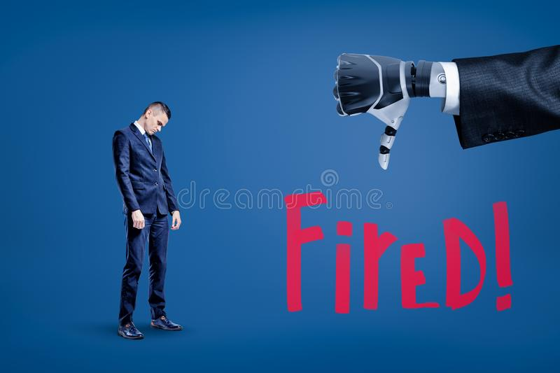 Sad businessman looking down and big close-up of robot`s hand doing thumbs down with title Fired below. Underperformance and dismissal. AI replaces people at stock images