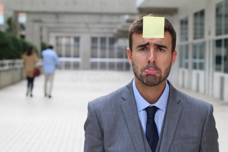 Sad businessman with a note on his forehead royalty free stock photo
