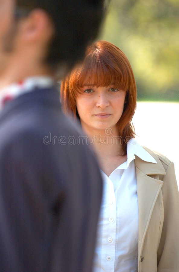 Sad Businesswoman. Young businesswoman outdoors with sad expression, as male coworker passes by royalty free stock photos