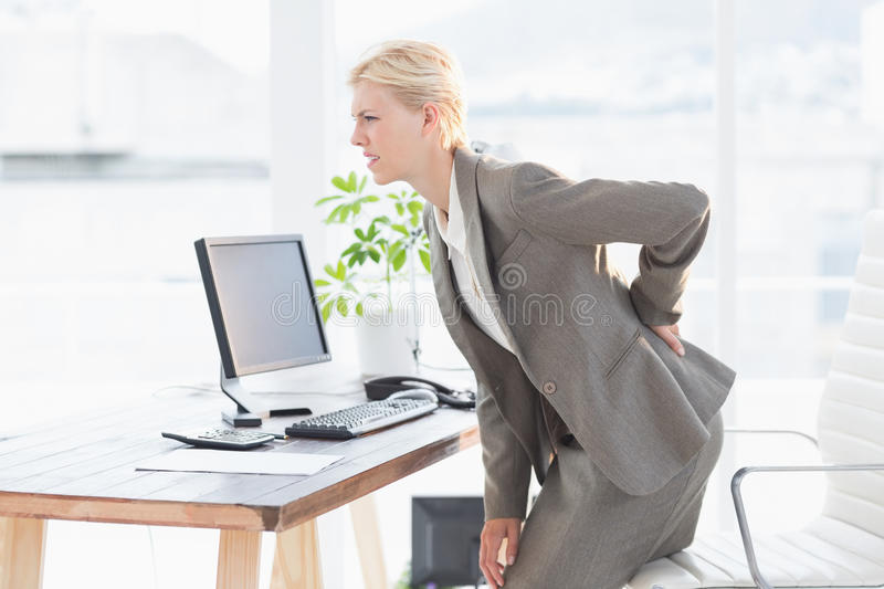 Sad businesswoman having back pain. In her office royalty free stock photo