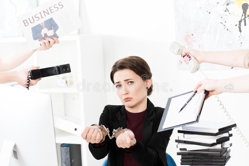 Sad businesswoman showing hands with handcuffs while secretaries holding newspaper, telephones and clipboard. In office royalty free stock image
