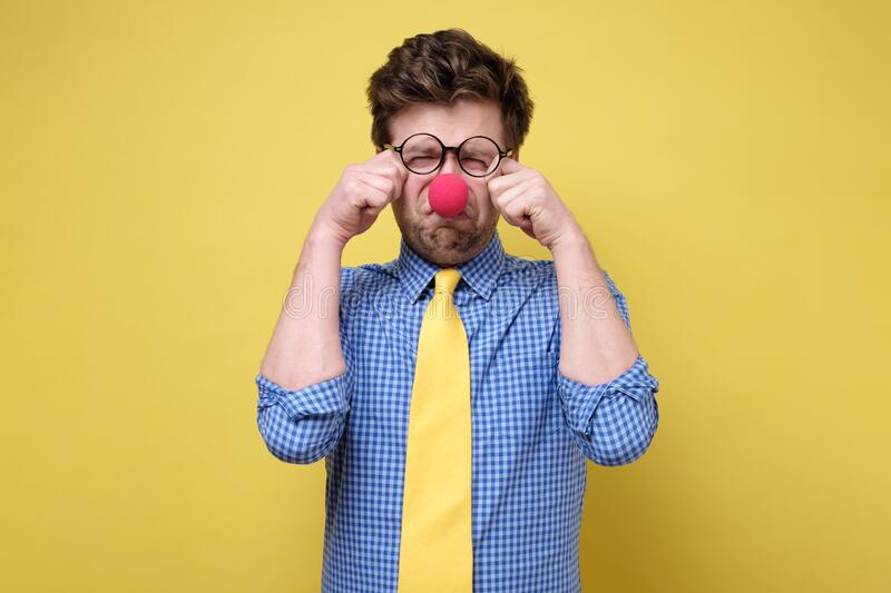Sad caucasian man dressed as clown crying against a yellow background stock photo