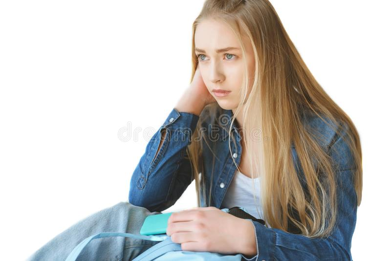 sad caucasian teenage girl with smartphone and backpack stock photos