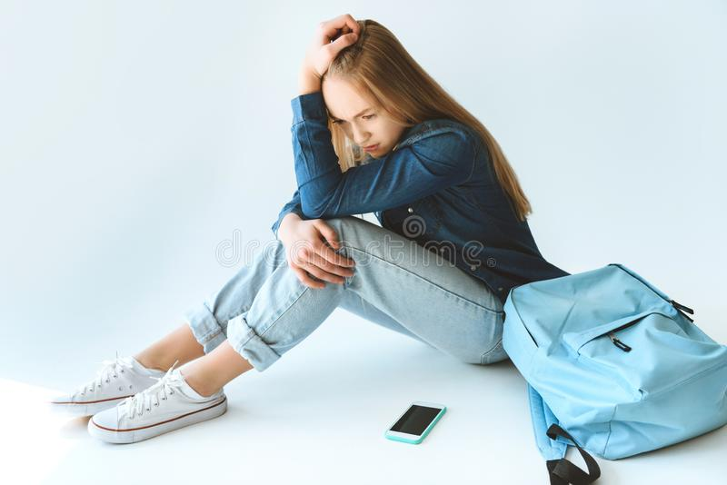 sad caucasian teenage girl with smartphone and backpack stock photo