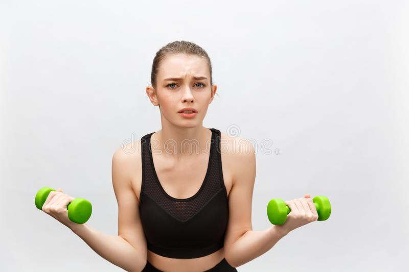 Sad Caucasian young woman with long medium brown hair in casual outfit holding dumbbell - Isolated stock photo