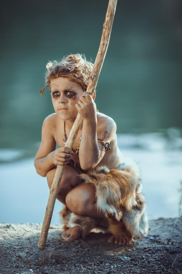 Sad caveman, manly boy with staff hunting outdoors. Ancient warrior. Sad caveman, manly boy with staff hunting. Prehistoric tribal boy outdoors on nature. Young stock image