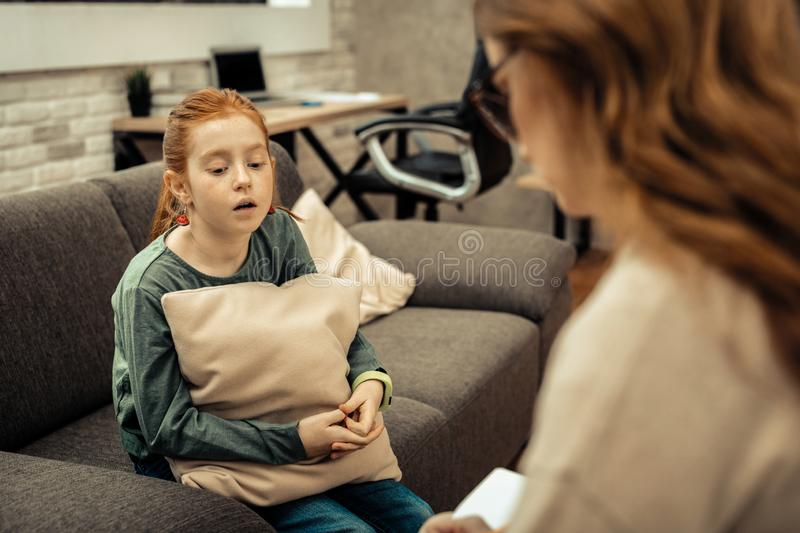 Sad cheerless girl speaking about her difficulties in life. Childhood problems. Sad cheerless girl speaking about her difficulties in life while having a session stock image
