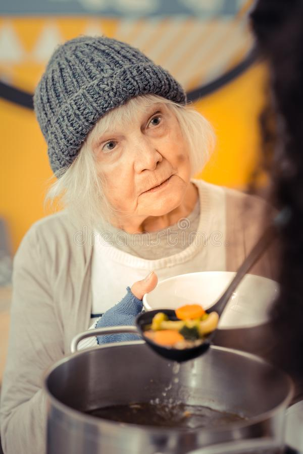 Sad cheerless woman asking for the soup. Hungry life. Sad cheerless women asking for the soup while coming to the volunteer center stock photo