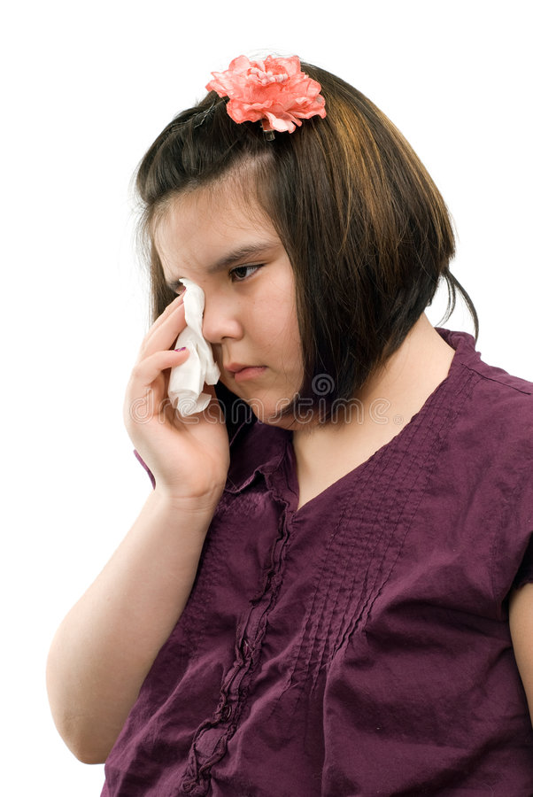 Sad Child. A sad girl is wiping her eyes with a tissue, isolated against a white background stock photos