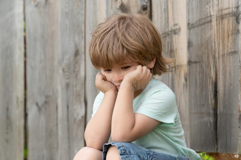 Sad child. A boy sits near a wooden fence. Preschooler and Autumn. Sad thoughts. Frustration. royalty free stock photo