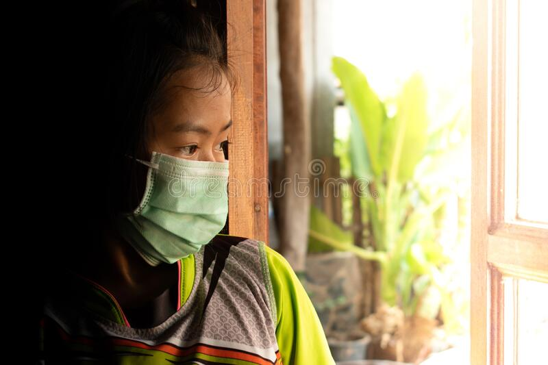 Sad child girl in protective medical mask standing at the window and looks out window. stock photos