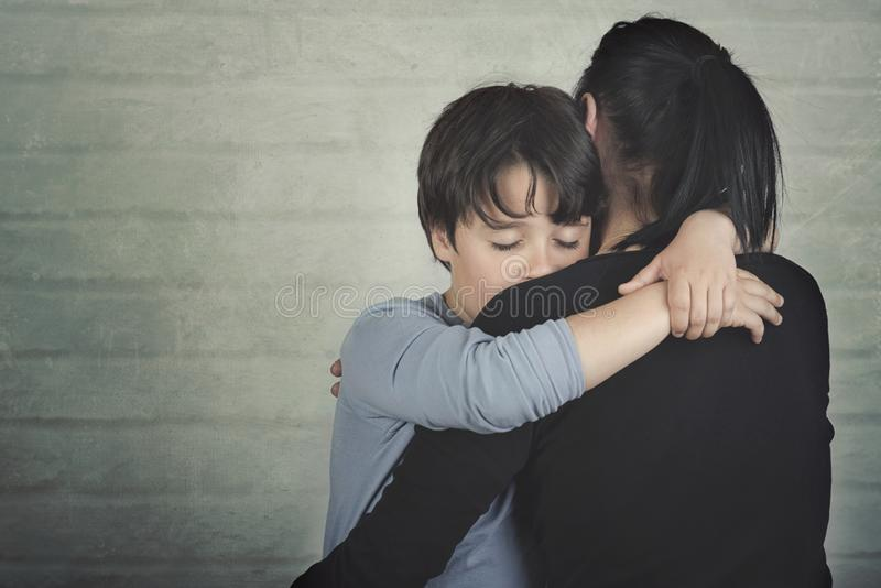 Sad child hugging his mother. On brick background royalty free stock images