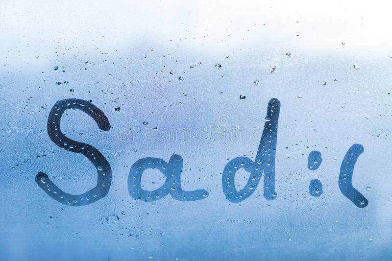 The sad child inscription on the blue evening or morning window glass stock photo
