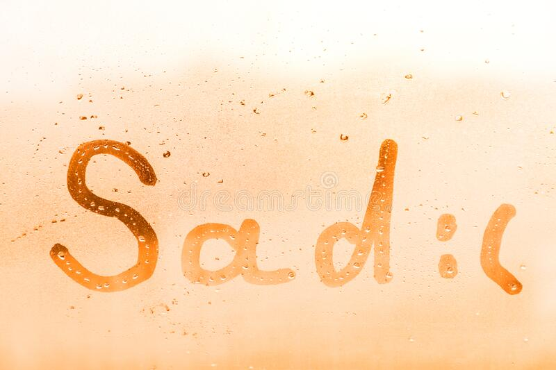 The sad child inscription on the orange or pink evening or morning window glass. With drops royalty free stock photo