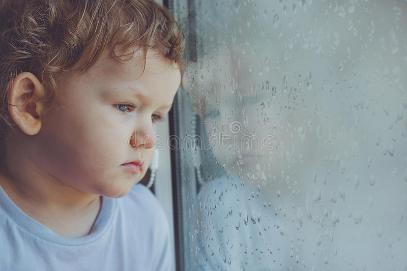 Sad child looking out the window with wet glass autumn bad weather. royalty free stock photos