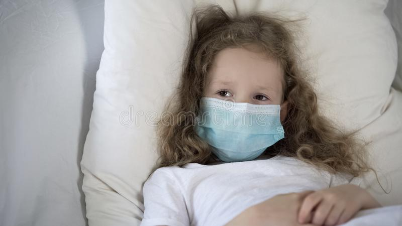 Sad child in medical face mask lying in bed, suffering rare disease, epidemic royalty free stock photos