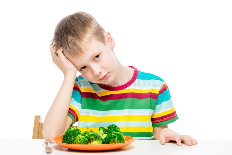 Sad child with a plate of broccoli at the table royalty free stock photo