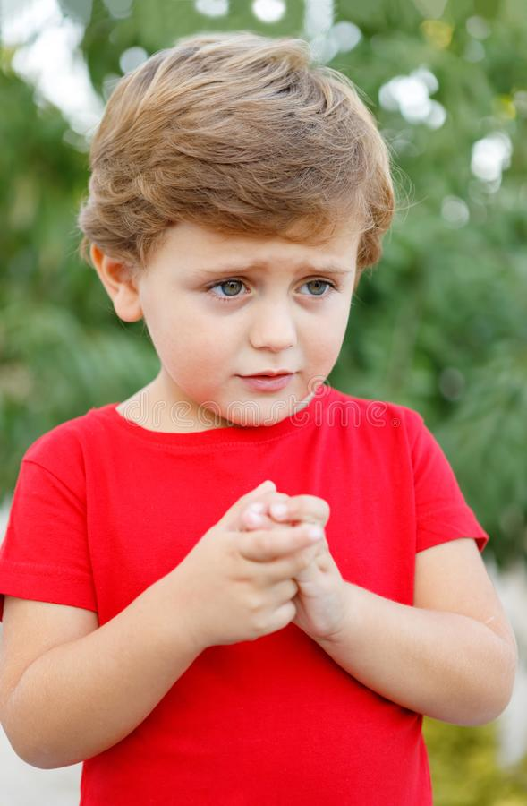 Sad child with red t-shirt. In the garden royalty free stock image