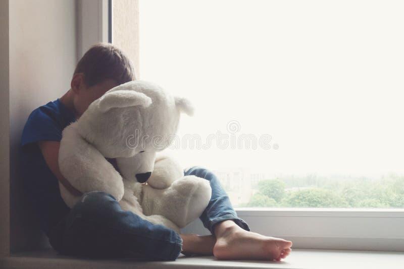 Sad child sitting on window stock image