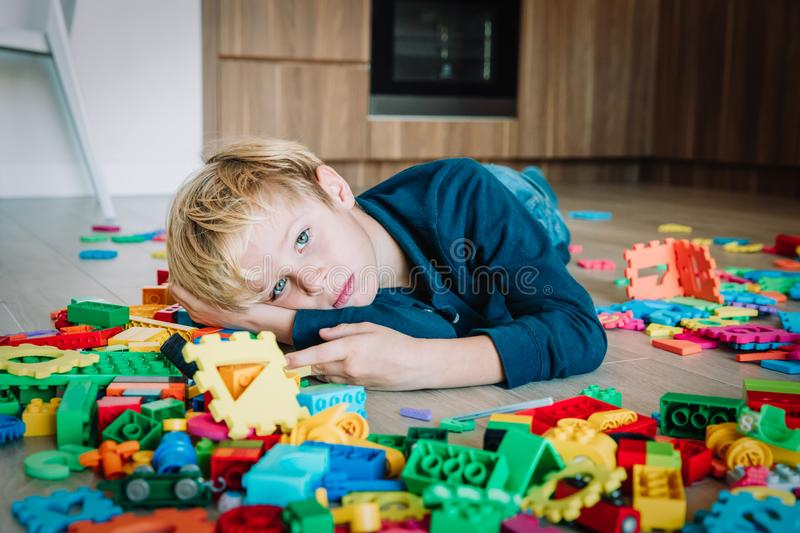 Sad child, stress and depression, exhaustion with toys scattered around. Boring at home stock image