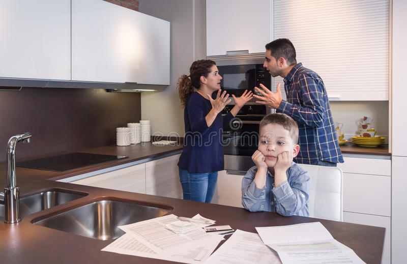 Sad child suffering and parents having discussion. Sad child suffering and his parents having hard discussion in a home kitchen by couple difficulties. Family royalty free stock photo