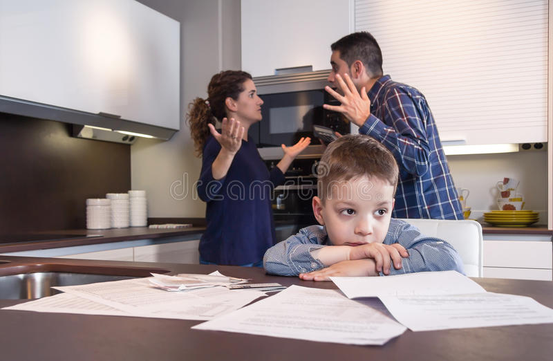 Sad child suffering and parents having discussion. Sad child suffering and his parents having hard discussion in a home kitchen by couple difficulties. Family royalty free stock photography