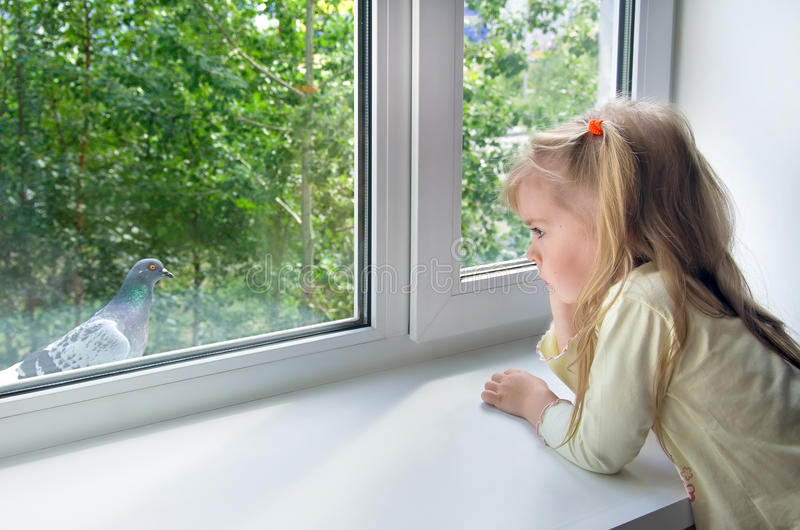Sad child at the window royalty free stock photos