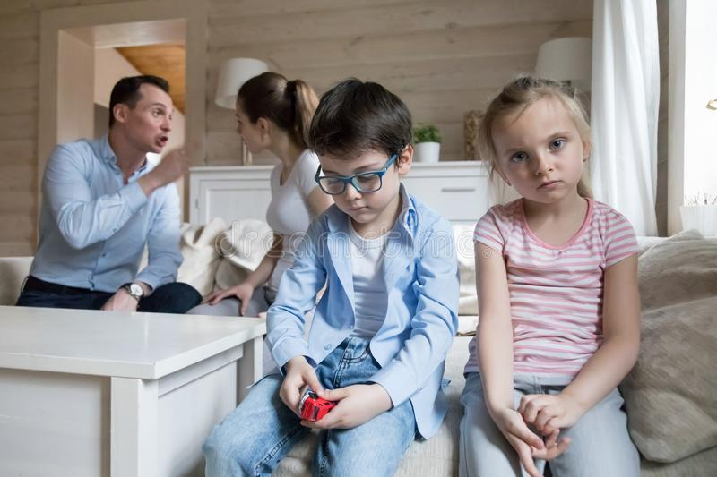 Sad children listen parents have angry fight at home headshot stock image