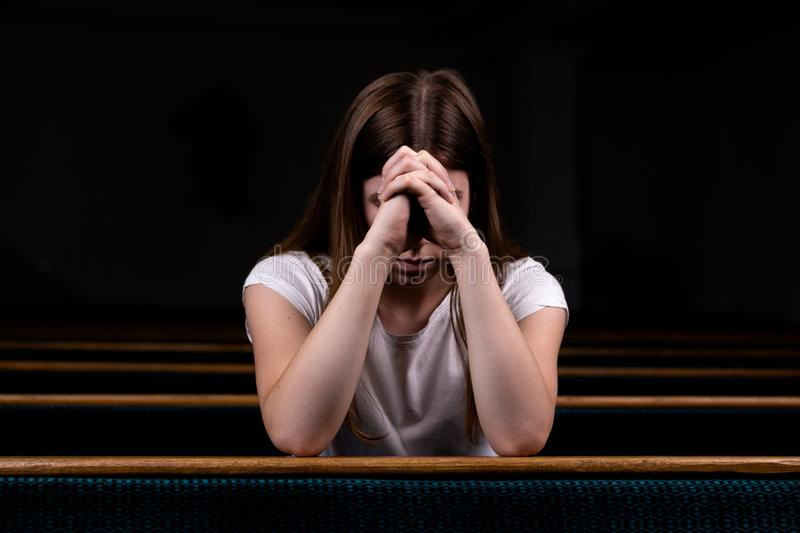 A Sad Christian girl in white shirt is sitting and praying with humble heart in the church royalty free stock photo
