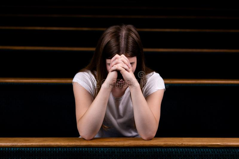 A Sad Christian girl in white shirt is sitting and praying with humble heart in the church royalty free stock photos