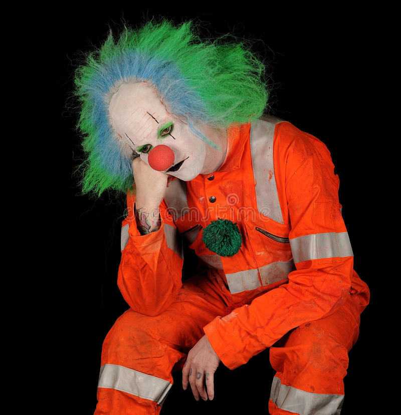 Sad Clown on Black Background. Sad clown in safety orange costume on black background stock photo
