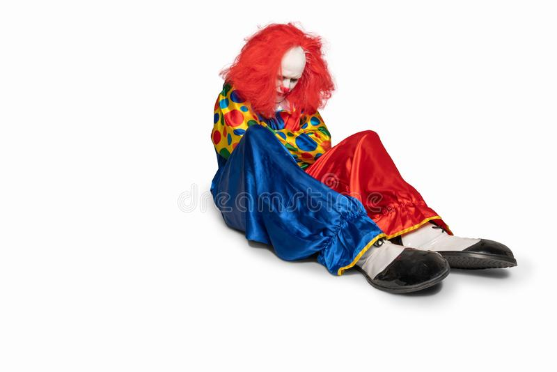 A sad clown is sitting on the floor looking down stock photo