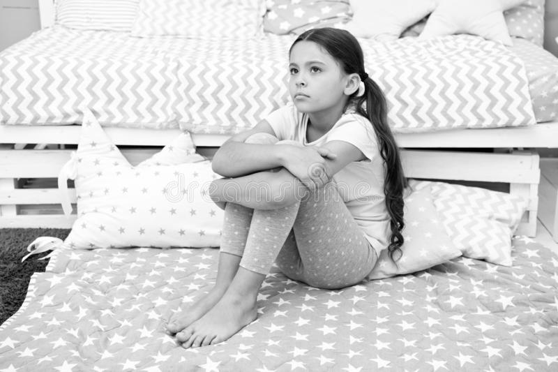 Sad concept. Sad little girl. Sad child sit on bed. Sad kid in bedroom at home. I want to play.  royalty free stock photo