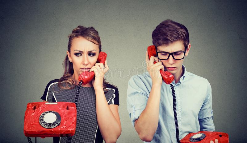 Sad confused young couple man and woman talking to each other over the phone royalty free stock photography