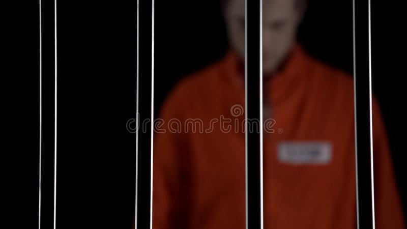 Sad convict standing behind prison bars, feeling regret about committed crime. Stock photo stock image