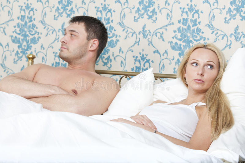 Sad couple in bed royalty free stock photography
