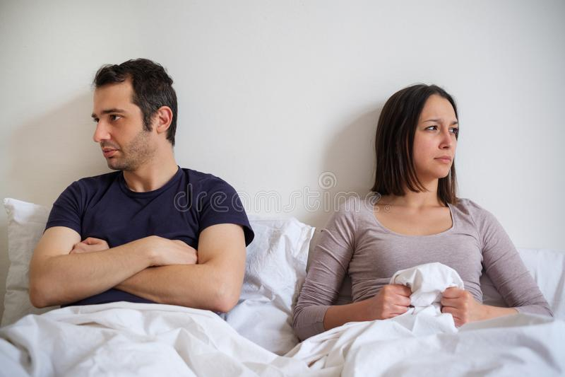 Sad couple in the bed depressed for sexual problem. Couple after arguing and fight lying in bed don`t make peace royalty free stock photography