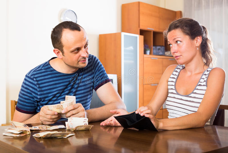 Sad couple counting budget. Young women and her husband counting budget for a month royalty free stock photography