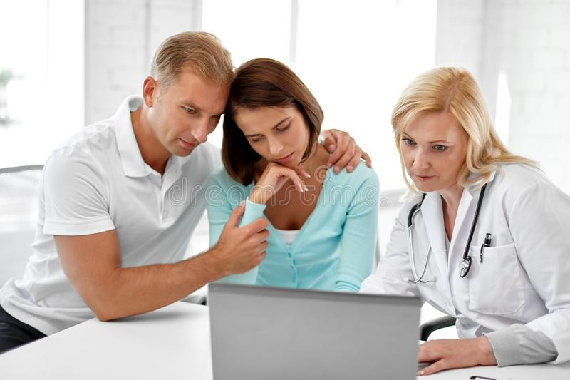 Sad couple and doctor at family planning clinic royalty free stock photos